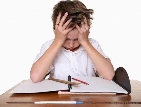 child-in-white-frustrated-while-looking-at-paper-on-desk